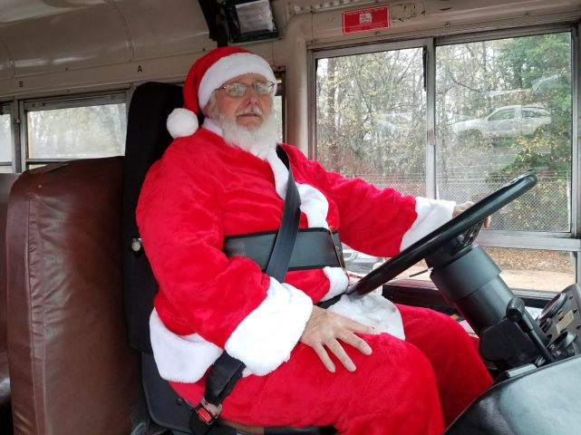 Santa Spreads Christmas Cheer at the Wheel of a School Bus