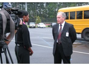 Hugh Hattabaugh, chief operating officer for Charlotte-Mecklenburg Schools, talks to a reporter about the district's new magnet shuttle stops.