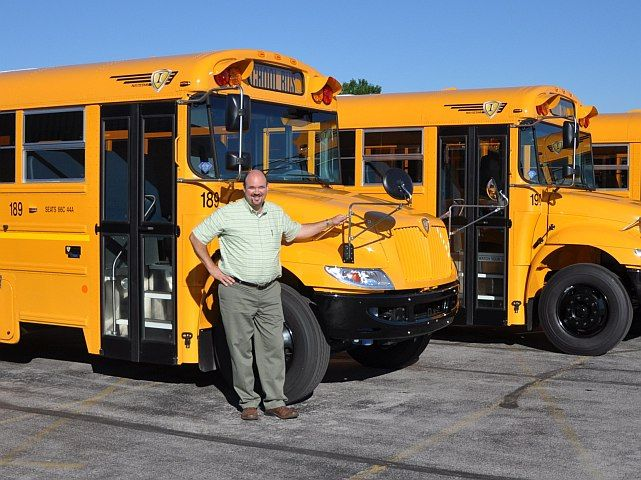 Shown here with some of the buses inHoneoye Falls-Lima Central School District's fleet is Bill...