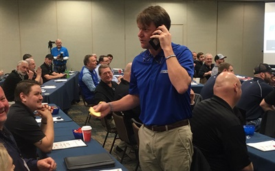 "Reinvestment will be a top Black's Tire priority in 2020. ""The world is changing,"" said Ryan Benton (standing), who took a real-time call from a customer during the meeting's kick-off session. ""But if we change with it, we'll grow."""