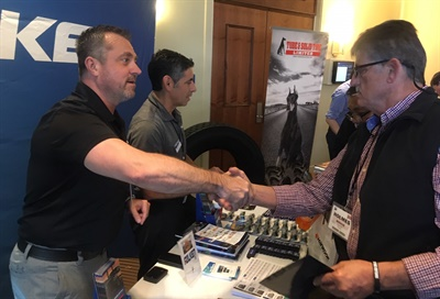 "Holmes Mishue, Black's Tire outside commercial sales manager (right), shakes hands with Tim Hutchison, Sumitomo Rubber North America account manager. ""The connections we make with suppliers are very important,"" said Mishue."