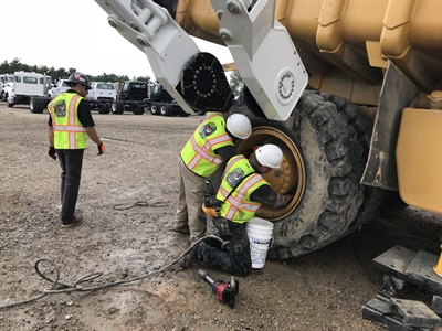 The tire handler helps position the tire on the hub so students can install and then torque the lug nuts during a TIA Earthmover Tire Service training class.