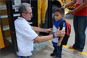 Bus Buddy Billy Huggins checks the nametag of a student at Matzke Elementary School as he prepares to board the bus during the first week of school last week.