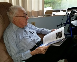 """Lloyd Stoyer held the late Les Schwab in the highest regard. """"He was probably the best tire dealer of the lot,"""" said Stoyer, pictured at his desk in Akron, Ohio, in 1994 (left) and reading MTD at his home in Canal Fulton, Ohio, in September 2017."""