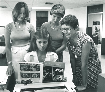 As part of a promotional photo, Karen Runion, seated, checks out the July 1977 issue of Modern Tire Dealer flanked by, from left to right, Cindy Ott, Patty Zettler and Donna Lake.
