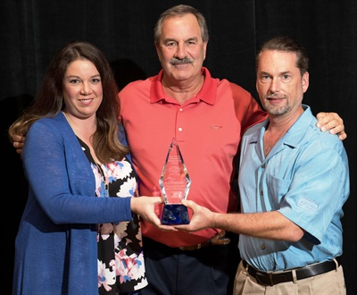 Ashlee Arnold presented her father, Jim Arnold (center), with the Art Fisher Memorial Award award along with Bo Fisher, chairman of Federated Auto Parts.