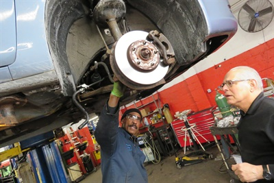 Godfrey Williams, left (with Barry Steinberg), looks for the cause of a banging noise the driver complained about. He determined a lower control bushing was the culprit, and sent the client a video of the complete multi-point inspection. Courtesy of Clark Goodpaster/Direct Tire