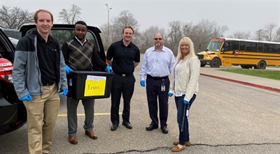 Hickman Mills C-1 School District enlisted ALC Schools staff (shown here with Teresa Tanner, director of student services for the district, right) to handle curbside delivery of meals to special-needs students. Photo courtesy ALC Schools