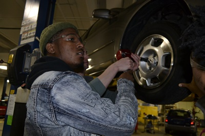 Cardeyair'e Trammell is learning hands-on skills, including how to mount tires, as a junior in high school. Bridgestone has outfitted a portion of the automotive classroom at East Community Learning Center in Akron with a small showroom and customer waiting area, and later this year students will open the doors to their own Firestone Complete Auto Care store to the public.