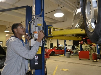 Zaveon Carter operates a lift inside the East Community Learning Center's automotive classroom. Trammell is a junior, and in the first year of a two-year program.