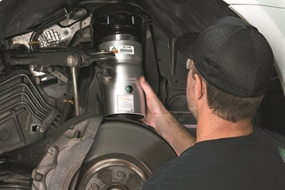 A technician installs a new replacement air suspension strut into the front of a Range Rover Sport.