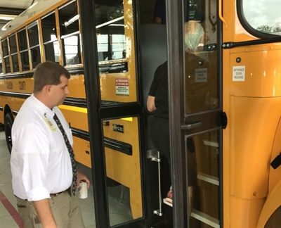 Banyon Allison, the transportation director for Calhoun County (Ala.) School District, hosted an open house to show the complexities of running a transportation department. Shown here, Allison, left, and a school board member board one of the district's new school buses.
