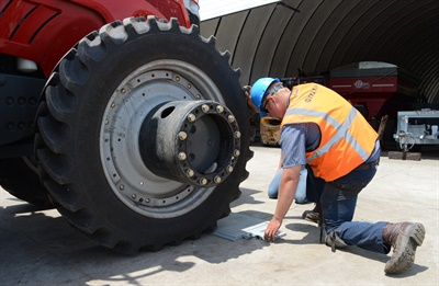 Alton Degenhardt places portable scales under each tractor tire. Knowing the weight exerted by a tire on the surface of soil enables him to calculate the air pressure needed to optimize the tractor's performance and reduce compaction. He also uses the scales to determine the correct weight split of the tractor.