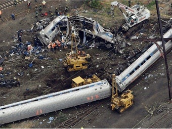 Two passenger cars on their side and the remains of a damaged passenger car. Photo: NTSB
