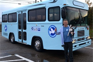 Bob Votruba and his canine companion, Bogart, are pictured with their new bus that was donated by Blue Bird Corp. for Votruba's organization One Million Acts of Kindness.