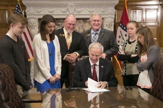 Hannah Alder (far right) watched on March 6 as Arkansas Gov. Asa Hutchinson signed a school bus seat belt bill that stemmed from Alder's 4-H project. Photo by Ryan McGeeney/U of A System Division of Agriculture