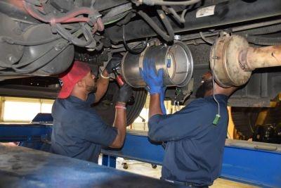 Tashard Jackson (left), an Atlanta Public Schools fleet mechanic, and Vince Parks, master fleet technician, install a diesel particulate filter together.