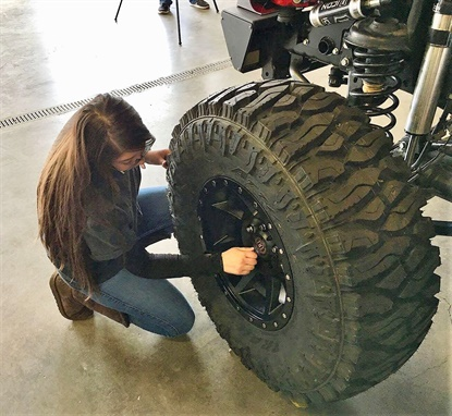 A student fromSanta Fe ECO High School in Santa Fe, N.M., adjusts the Atturo tires ona customized Jeep for a SEMA-sponsored project in 2018. The program will expand to five vehicles and high schools in 2019.
