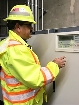 Balvir Thind, a Principal Electrical Engineer, is shown inspecting a new uninterruptible power supply set-up at 19th St./Oakland Station.