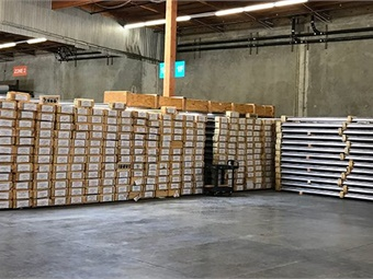 New, stainless steel-capped aluminum third rail segments stacked in a warehouse. BART