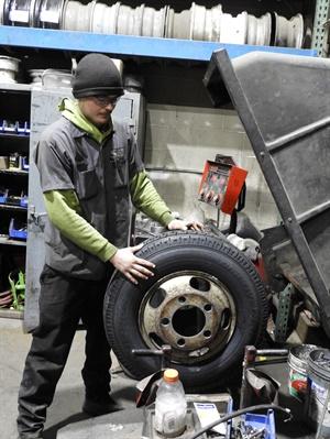 Carson Hancock balances a light truck tire.