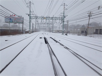 A switch heater when it is switched on prevents snow and ice from accumulating on the switch where two sets of rails come together. The dark area in the center of the photo shows that the snow has been melted so that track switches will work properly. Switches are pieces of running rail that move, allowing trains to change from one track to another. Photo by Melvin Donegal, Metro-North Assistant Signal Inspector,