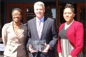 Blue Bird President and CEO Phil Horlock accepts the Extra Mile Award from the Middle Georgia Clean Air Coalition. He is pictured with the coalition's Charise Stephens (right) and a volunteer.