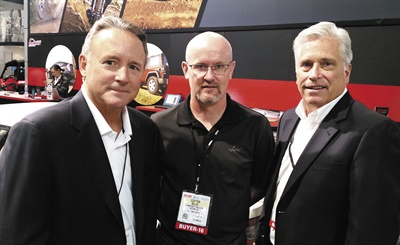 Independent Tire Dealer Group executives Mike Cox, left, and Ed Long, right, walk the trade show floor with ITDG Chairman Clayton Miller, owner of Mainstreet Tire USA Inc. in Peyton, Colo.