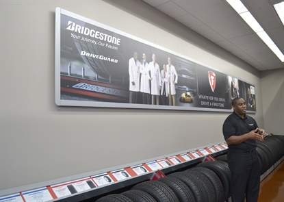 In this June 2016 photo Damien Harmon talks about the redesigned Firestone Complete Auto Care lab store in St. Charles, Ill.