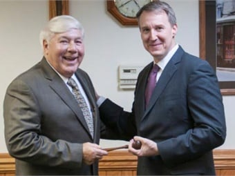 Brookville CEO and Chairman Dalph McNeil (left) passes the symbolic gavel to President Rick Graham.