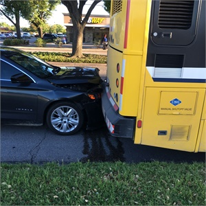 A car rear ended a parked bus while the operator was using the restroom at a nearby fast food restaurant.