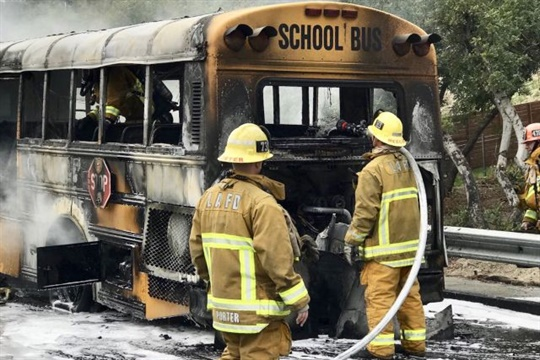 Authorities say that a school bus driver noticed smoke and pulled to the shoulder, and four adults assisted 23 children in safely evacuating before firefighters arrived. Photo courtesy CHP West Valley