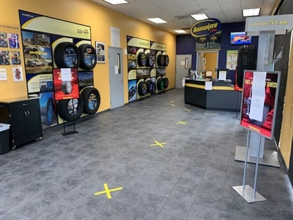 """X"" marks the spots where customers should stand inside Mountain View Tire's stores."