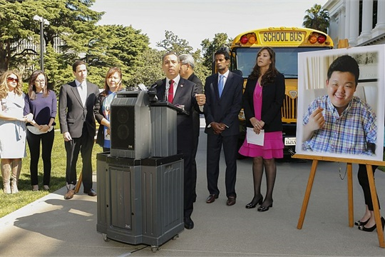 """Gov. Jerry Brown signed the """"Paul Lee School Bus Safety Law,"""" which will require all school buses in the state to be equipped with child-check reminder alarm systems and for bus drivers to be trained on those systems. Shown here at the podium is Sen. Tony Mendoza, the author of the bill, at a press conference in April."""