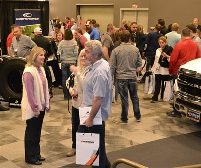 Cheryl Gossard, left, greets K&M Tire customers as they enter the trade show during the tire distributor's 2019 dealer meeting in Dallas.