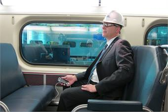 Alex Clifford, executive director/CEO, Metra, charging his phone at one of the new power outlets in a renovated railcar.