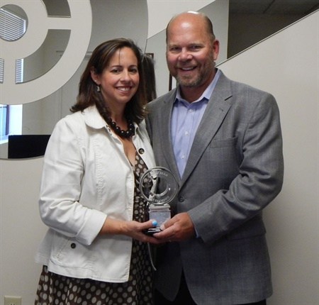 Angela and Chris Chase display the award Goodyear presented to them in honor of Rice Tire selling Goodyear brand tires for 44 of its 60 years. Chris is Rice Tire's CEO.