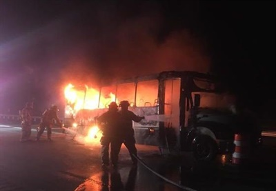 The rear tire of this bus, owned by Illinois-based Herscher Christian Church, caught fire. All 18 passengers were able to exit unharmed as the fire quickly spread through the rear of the bus.