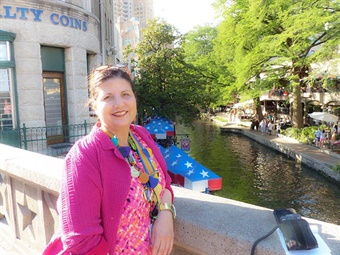 Christine Viña wearing her pins and medals, by the famous San Antonio Riverwalk in 2016. Photo credit Laura Lee Huttenbach.