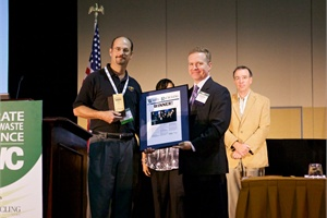 Mike Strickland, environmental health and safety manager for Collins Bus Corp. (left), accepts the Green Corporate Citizen Award on behalf of the company at the Corporate Recycling & Waste Conference.