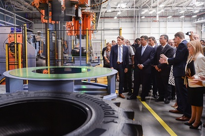 A group stops at a curing machine during a tour of Continental's farm tire production center in Portugal. By the end of 2017 the factory will produce 5,000 tires in 13 sizes