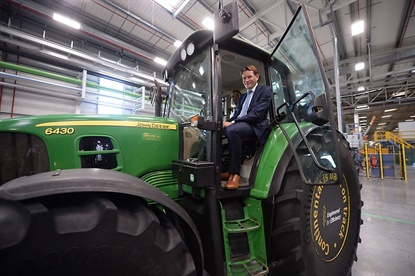 Nikolai Setzer, head of Continental's tire division, hops aboard a tractor during an event at the company's new farm tire production center.