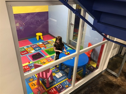 The play area is filled with toys and games, but also has large windows so parents can keep an eye on their children while they wait for tires and automotive service.