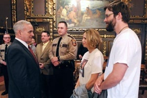 At a crossing arm bill signing ceremony, Minnesota Gov. Mark Dayton speaks with the parents of Evan Lindquist, who was struck and killed by his school bus in 2010. At center are MSBOA President Doug Grisim and state director Lt. Brian Reu.