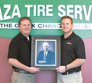 """A photo of Vernon """"Pee Wee"""" Rhodes hangs in the lobby of the Plaza Tire headquarters, and a box full of his green business cards remains on display in the training center."""