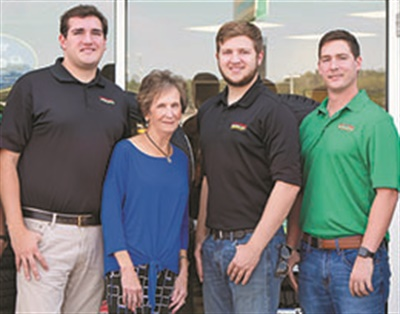 Carole Rhodes and her husband founded Plaza Tire. Here she poses with the potential leaders of the third generation to continue the family business, from left, her grandsons Sam Rhodes, Zach Rhodes and Casey Holloway.
