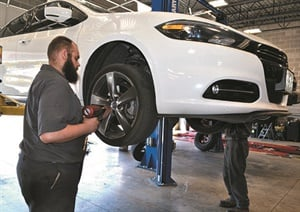 Dustin Knupp works to remove a flat tire from a customer's vehicle at the Plaza Tire store in O'Fallon, Mo. It's the newest Plaza Tire location in the St. Louis market.