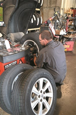 """Some shops are just naturally harder on equipment, especially tire changers and balancers,"" says Plaza Tire's Mark Rhodes. (Pictured: Tire technician Travis Smith balances a set of tires.)"