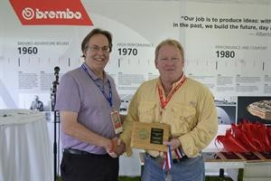 Modern Tire Dealer Editor Bob Ulrich, left, accepts the IAMC gold medal awarded to Senior Editor Joy Kopcha from Mark Phelan of the Detroit Free Press.