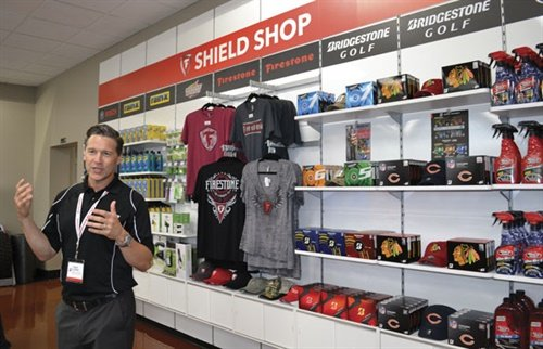 Trent Stoner, director of brand strategy, says for the first time the company is selling Bridgestone and Firestone gear in its stores. The Shield Shop features clothing and golf balls, plus more traditional automotive products like windshield wipers.